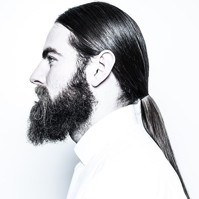 Sleek Low Ponytail + Full beard - men's haircuts